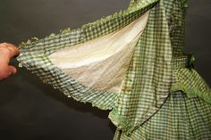 Later 1860s green-and-cream checked silk dress with peplum belt, trimmed with green silk taffeta. Unusual combination of pagoda sleeves opening at back over coat sleeves. I have seen this in fashion plates with the pagoda opening to the front, not the back.