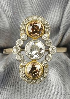 An Edwardian Coloured Diamond and Diamond Ring. Bezel-set with an old European-cut diamond, further set with two old European-cut coloured diamonds, old European- and rose-cut diamond accents, platinum-topped 18kt gold mount.