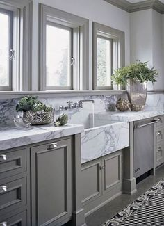 Integrated Marble Sink - 3-inch-thick marble countertops with simple eased edge create a seamless look along the window wall. The grey of the cupboards and floor make an awesome pairing with stainless steel appliances and marble countertop.