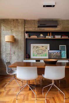 Decoração de apartamento com concreto na sala de jantar, obras de arte, com pinturas, cadeiras brancas, mesa de madeira, adornos.