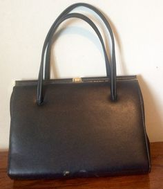 A large navy blue leather handbag from the 50s or 60s with a string gold clasp. Blue material lining with makers label, 2 internal zipped compartments and internal side pocket. There is some wear (as shown) and some slight damage at the base, hence the lower price. Still a good quality bag for everyday use or as a stage prop.  Measurements: 11.5/30cm wide 8/30cm high without handles 14.5/37cm high with handles 2.2/6cm deep  Please note: We are happy to post our vintage items anywhere in the…