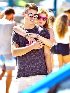 Bella Thorne 'n' Gregg Sulkin snuggled up in shady style! Hot pink sunnies for her and flashy frames for him!