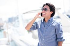Business man on the phone by his yacht stock photo