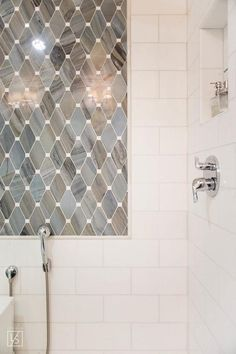 Gorgeous walk-in shower is fitted with white subway wall tiles framing a tiled niche and complemented with gray marble diamond accent tiles positioned above a polished nickel sprayer.