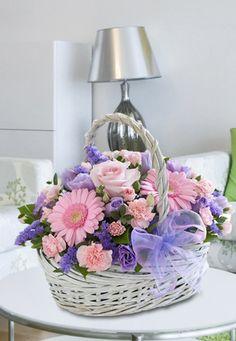Composizione in cesto con lisianthus, gerbere, una rosa rosa
