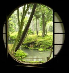 A round door with sliding shoji screens opens on to a beautiful, green garden.