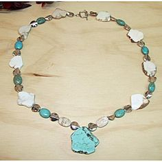 Unusual nuggets, ovals and flat free-form pieces of white turquoise with brown mottling and ovals of blue turquoise decorate this necklace. The Turquoise Trophy necklace by Susen Foster secures with a toggle clasp.