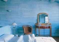 Dormitorio de una casa de pueblo del Ampurdán. El azul se despliega por todos los elementos con cabecero de obra incluído. Esto permite que los muebles de madera y fibra resalten con fuerza.