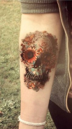 forearm tattoo of a dreamy pastel botanical collage forming a skull