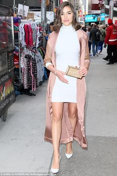 Olivia Culpo wearing Stephanie Rad White Stretch Knit Mock Turtleneck Dress, House of CB Coryn Duster Coat and Christian Louboutin So Kate Pumps