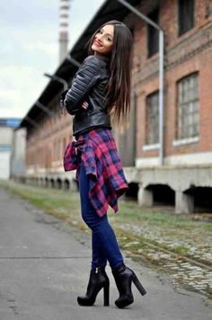 Black leather jacket and boots with plaid shirt and blue jeans.