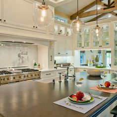 bright white kitchen features over sized dark island and fanciful round pendant lighting