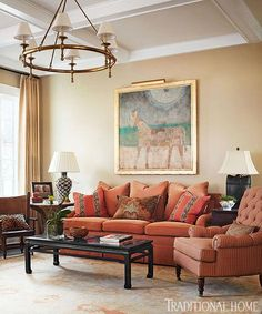 """{A scene from the O'More Designer Show House, featured in @Traditional Home's July/August 2013 issue} The hues are repeated in the sofa, club chair, an antique-looking Oushak rug, and artwork, including portraits of Simmons's own children. """"We wanted the room to be comfortable and inviting as well as have an interesting mix of textures, styles of art, furnishings, and materials,"""" Simmons says."""
