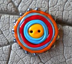 I made this button using bright opaques of orange periwinkle, dark turquoise, red and Double Helix Aurae raised dots on the edge. A fun button to add to anyone of a kind garment or bag!  Button measures approximately: 40mm at widest point  My buttons are made on a two hole button mandrel and go directly from the torch to my Chili Pepper kiln for proper annealing. Beads are cleaned of bead release and carefully packaged for shipping. Thanks for looking!! SRA #R114