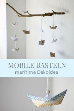 Maritime Dekoidee: DIY für ein Papierboot Mobile. Ein Mobile selber basteln ist leichter als gedacht. Ihr müsst lediglich Papierschiffchen falten, auffädeln und an einen Dekoast knoten. Die maritime Deko eignet sich als Kinderzimmer Dekoidee, als Badezimmerdeko oder auch als Babyzimmer Deko. Das Mobile basteln kann man auch mit Kindern. Es ist ein einfaches Origami Mobile. Nautical Baby Nursery, Amelie, Mobiles, Origami, Diy And Crafts, Shabby Chic, Creative, Room, Handmade