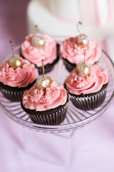 wedding cupcake on a transparent plate of chocolate cakes and pink cream with a gold cherry wedding cakes via instagram