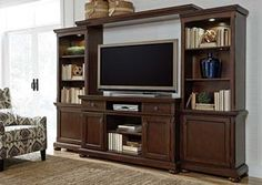 """With a rich rustic beauty radiating from the stylish details, the """"Porter"""" entertainment wall flawlessly transforms the atmosphere of any living room environment. The select cherry veneer is beautifully bathed in a burnished brown finish that flows over the framed details and turned bun feet to create an entertainment wall that perfectly captures the ideal of rustic design."""