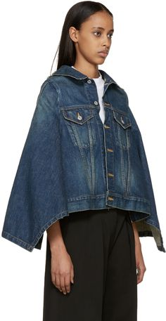 Long sleeve cape-style denim jacket in indigo. Fading throughout. Spread collar featuring cut-out at nape of neck. Button closure at front. Flap pockets at bust. Panelling at back. Asymmetric back hem. Silver-tone hardware. Contrast stitching in tan.
