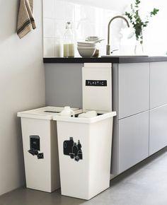 Deux grandes poubelles blanches à côté d'un plan de travail de cuisine, étiquetées pour le recyclage.