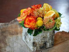 Orange roses, pincushion protea, billy buttons and lemon slices make a really cute flower arrangement