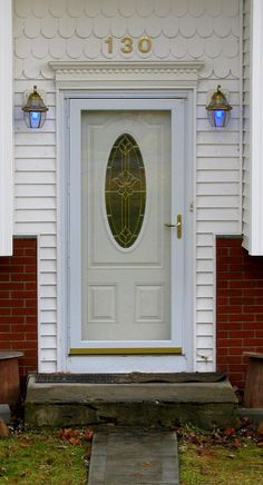Good With Oval Stained Glass Window, Storm Door, Doorbell, And Two Outdoor Lamps  With Blue Light Bulbs In Them. All Are On A Split Level House With A Half  Brick ...