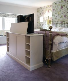 End of bed TV cabinet, TV raised: love this for new room layout planning with workout equipment on other side!