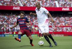 Steven N'Kemboanza Mike N'Zonzi (R) of Sevilla FC competes for the ball with Munir el Haddadi (L) of FC Barcelona during the La Liga match between Sevilla FC and FC Barcelona at Estadio Ramon Sanchez Pizjuan on October 3, 2015 in Seville, Spain.