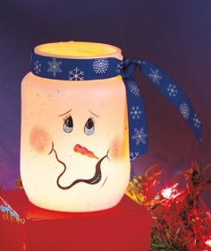 """Christmas Decor - Frosted Jar Snowman Candleholders - Blue Boy by ABC. $17.77. Glass. 4-1/2"""" x 3"""" dia.. Frosted Jar Snowman Candleholder puts any room in the holiday spirit. The expressive snowman face painted on the front instantly brightens any space. Add your own battery-operated tea light for a festive glow. A snowflake-patterned ribbon tops the jar. 4-1/2"""" x 3"""" dia. Glass. A lot of cheer in a small space!"""