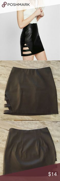 "Black Mini Skirt Express ""Minus the leather"" faux leather mini skirt with cut out on the side. Adds an edgy accent to a ""going out"" look. Looks amazing with a bodysuit. Worn once out. No flaws or defects. Shell/face: Polyurethane Back/Lining: 100% polyester Express Skirts Mini"
