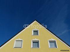 Schöne alte Fenster mit Gardinen und Rollladen in ockergelber Fassade in Markt Burgheim in Bayern