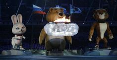 Giant robotic mascots gather around the Olympic flame before extinguishing it during the closing ceremony of the 2014 Winter Olympics, Sunday, Feb. 23, 2014, in Sochi, Russia.