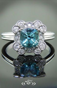 Beautiful ruffled halo mounting with light blue sapphire in ceter set.