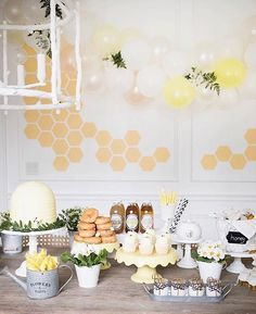 Hexagon wall decals of gold placed in a honeycomb pattern on a white wall behind a beautiful decorated table with cupcakes and sweets.