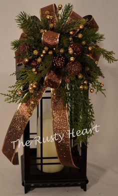 This swag is decorated with bronze ribbon, various greens, berries, and pinecone ornaments .