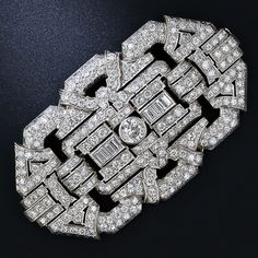 This glittering and impressive 1930s vintage Art Deco brooch evokes old Hollywood glamor. The over size platinum diamond plaque (3 1/3 inches by 1 3/4 inches) features a central bright-white and sparkling European-cut diamond weighing 1.25 carats. The diamond is flanked by eight channel-set baguette-cut diamonds and is further set with 270 round cut diamonds bringing the total diamond weight to 13.50 carats.