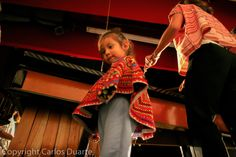 A girl waits alongside her mother as she plays the Marimba during an all women´s concert in a Local Theater, in Guatemala City.