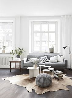 Living room: white walls, white window frames, light grey sofa, dark timber floorboards, grey knit pouffe/ottoman