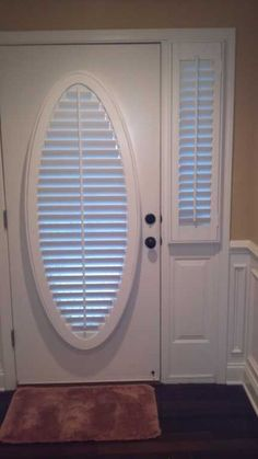 "A front door with an oval window beautiful covered with  2½"" Louverwood Plantation shutters from The Louver Shop.  The interior shutters on the front door are complemented by the shutters on the sidelight."