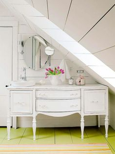 Vintage Cottage Under the Eaves Space-saving moves and budget-friendly materials add function and style to this small attic bathroom. An old sideboard-turned vanity tucks neatly beneath the eaves. The vanity's surface was gently aged, which blends well Small Attic Bathroom, Bathroom Design Small, White Bathroom, Small Bathrooms, Bathroom Ideas, Attic Shower, Loft Bathroom, Bathroom Designs, Bath Ideas