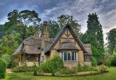Heading north, across the Channel to England, brings us to the enchanting English cottage pictured below.   A prominent bay window, multiple decora-tive  chimneys,  and  a varying roof line covered with thatch contribute to the irresistible charm of this picture book cottage!