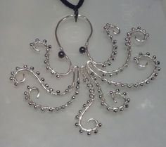 Hey look, heres a silver-plated wire octopus necklace with silver bead suction cups and hematite eyes! He obviously needs to live on your neck.