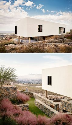 This modern house has a landscaped yard with stone walls. The house features black window frames that contrast the white exterior walls.