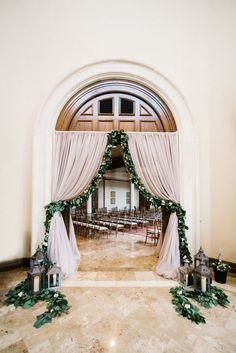draped wedding entryway featured a full garland of lemon leaf and seeded suclayptus, peppered with white and ivory spray roses. a trio of lanterns was set at each side of the entryway.