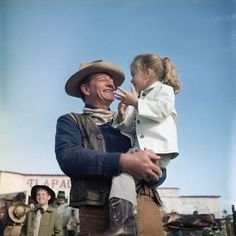 JOHN WAYNE and four-year old daughter Aissa on set in 1960.