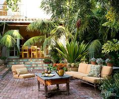 Reclaimed bricks in various sizes bring been-around-awhile appeal to an antique-furnished patio positioned amid tropical foliage. Newer brick-style tiles reface concrete steps to create a pulled-together design.