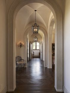 Tuscan Villa mediterranean hall. Loving the Herringbone and the arch door frames amazing!