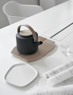 tea pot and base. minimal and modern and raw wood. with off shape white dish.