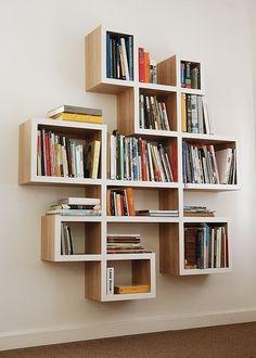 librería en madera qye se encuentra en el salón. Está cerca del sofá y tiene muchos libros.