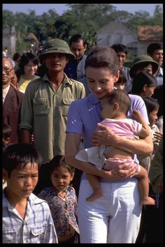 Audrey Hepburn is accompanied by children on a walk in the hamlet of Phuc Ly, Phu Minh Commune, Tu Liem District near Hanoi.   Audrey Hepburn's visit to Vietnam in October/November of 1990 contributed to drawing world attention to the needs of children in this aid- starved country.