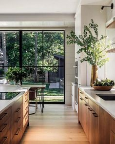 gorgeous natural woods and fresh greenery enhance this stunning modern kitchen design Mowery Marsh Architects Gorgeous kitchen decorating & design ideas, from cabinet choices to lighting, modern to classic, this gallery of kitchen images will inspire! Home Decor Kitchen, Kitchen Interior, New Kitchen, Home Kitchens, Kitchen Ideas, Modern Kitchens, Kitchen Layout, Kitchen Hacks, Contemporary Kitchens